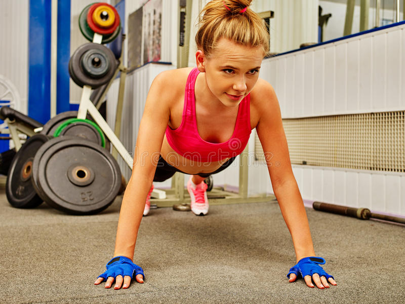 Stretching woman in sport gym. Girl doing push-up from floor . stock photos