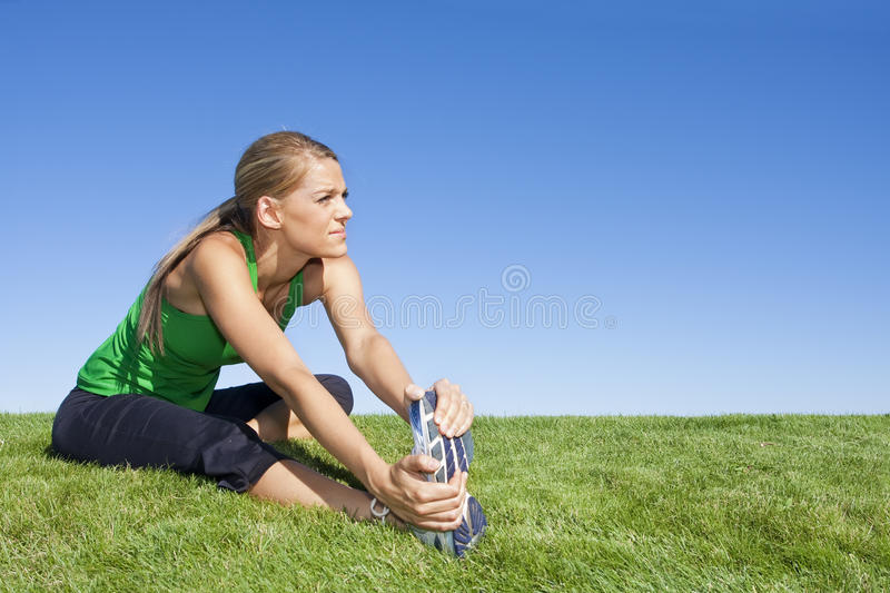 Stretching Before Workout. An attractive female runner stretching before her workout. Lots of Copy Space stock photography