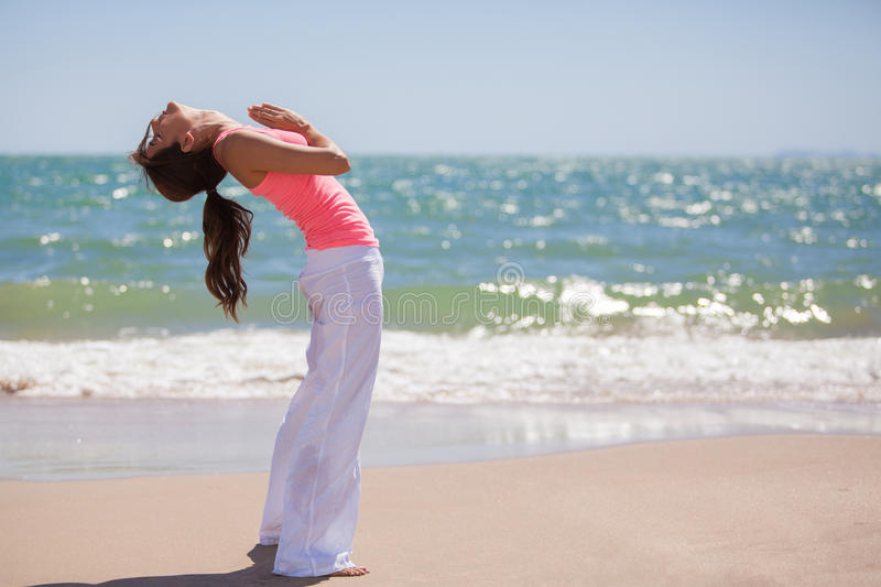 Stretching for yoga practice. Young woman doing some stretching exercises for her yoga practice at the beach royalty free stock photo