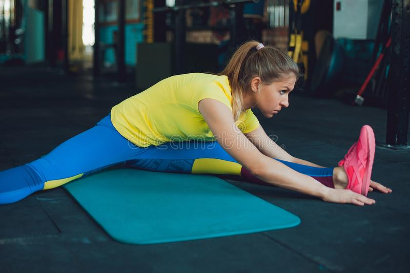 Stretching. Young woman in gym stretches stock photos