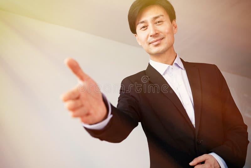 Stretta di mano d'offerta del giovane uomo d'affari asiatico attraente dopo l'affare di affari fotografia stock