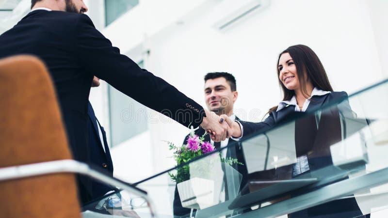 stretta di mano dei soci commerciali dopo la discussione sul contratto nel posto di lavoro in un ufficio moderno immagine stock libera da diritti