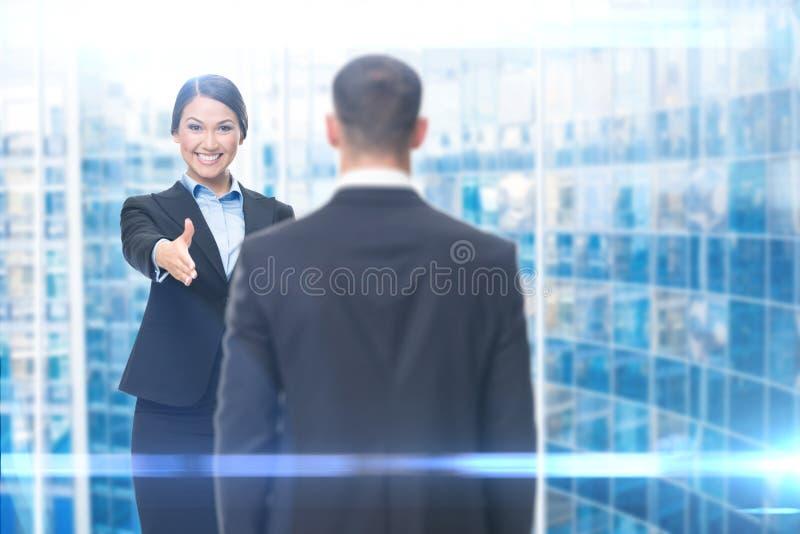 Stretta di mano della donna di affari che gesturing con il responsabile immagine stock