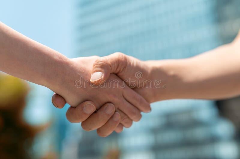 Stretta di mano della donna e dell'uomo con il fondo della città di affari fotografia stock libera da diritti