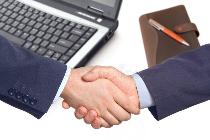 Stretta di mano di affari con un computer portatile e un blocchetto per appunti fotografia stock libera da diritti