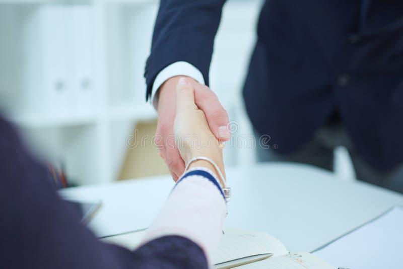 Stretta di mano maschio e femminile in ufficio Concetto serio di associazione e di affari immagine stock