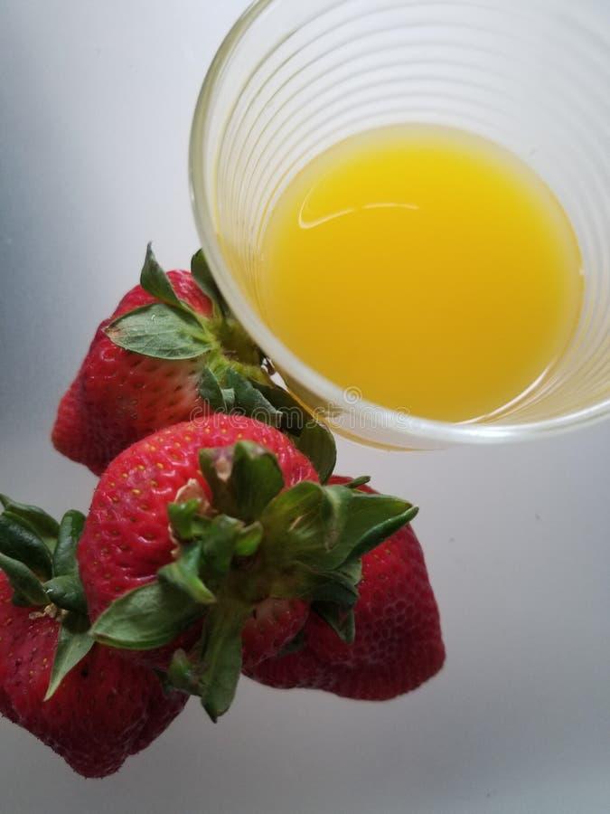 Strewberries e um vidro do suco de laranja fotos de stock royalty free