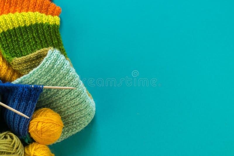 Stricken eines Regenbogenschal und -hut Blauhintergrundes lizenzfreie stockfotos