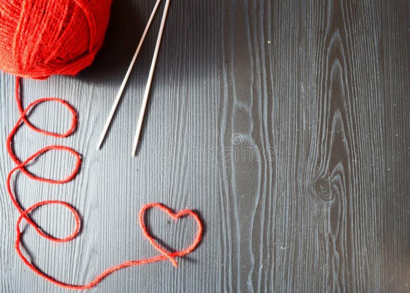 stricken Roter Faden auf hölzernem Hintergrund Stricknadeln stockfotografie