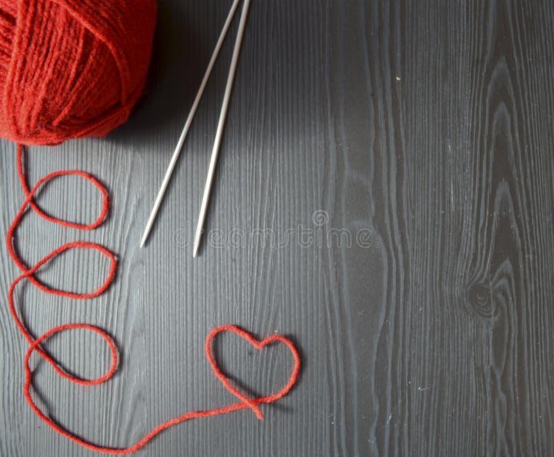 stricken Roter Faden auf hölzernem Hintergrund Stricknadeln lizenzfreies stockbild