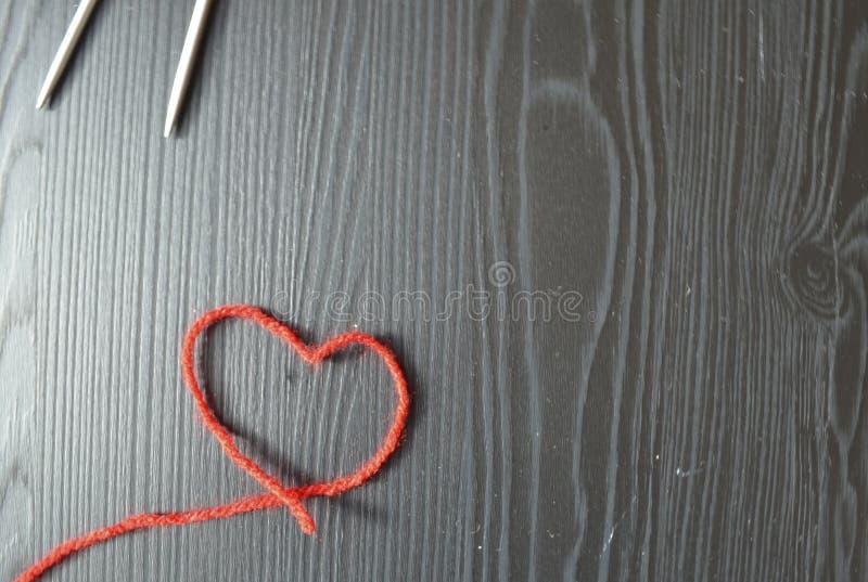 stricken Roter Faden auf hölzernem Hintergrund Stricknadeln stockfotos