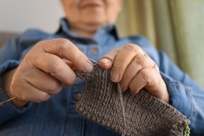 Strickende Strickjacke der älteren Frau zu Hause, Nahaufnahme stockfotografie
