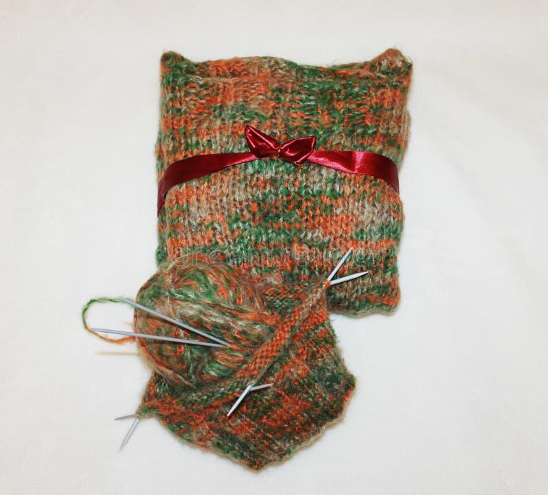 Strickender Thread mit Nadeln, mit einem Geschenk für kühles Wetter lizenzfreies stockbild
