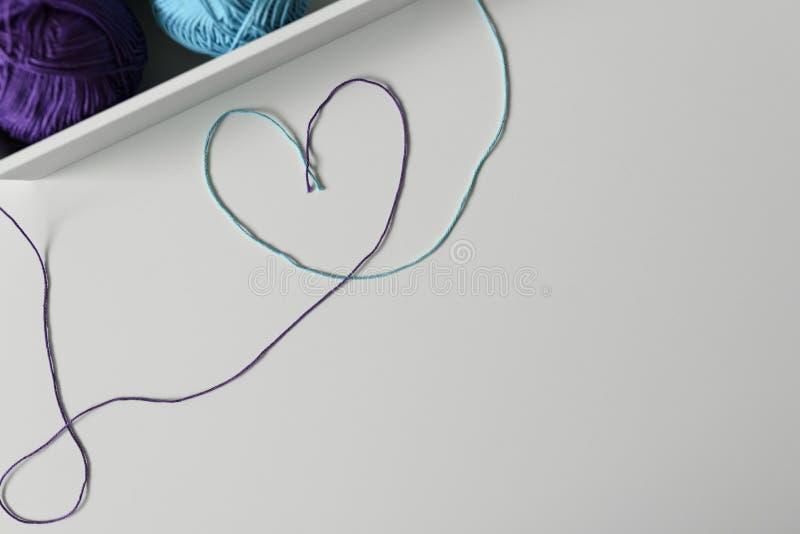 Strickgarnstränge verwendeten, um buntes Herzsymbol auf weißem Hintergrund mit Kopienraum zu entwerfen stockfotos