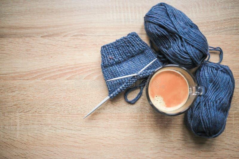 Stricknadeln, blaues Garn, schwarzer Kaffee sind auf dem Tisch lizenzfreie stockbilder