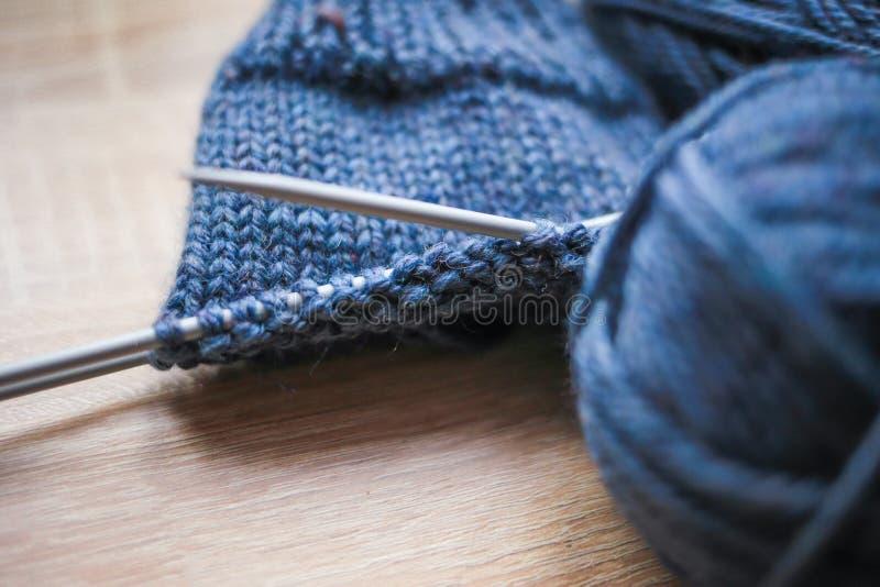 Stricknadeln, Schleifenzähler und blaues Garn sind auf dem Tisch lizenzfreies stockfoto