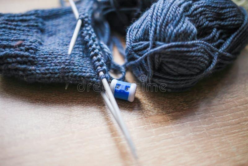 Stricknadeln, Schleifenzähler und blaues Garn sind auf dem Tisch lizenzfreie stockfotografie
