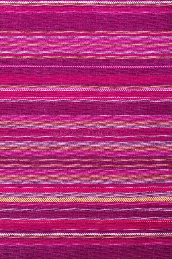 Strickte Stoffstruktur mit mehreren warmen Farben violett, violett, magenta, rosa, rot, maron, orange, gelb Nahaufnahme der stockfotos