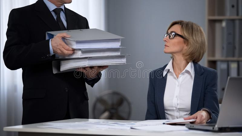 Strict boss overloading worker with work, prejudiced attitudes towards employees. Stock photo stock images