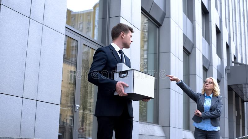 Strict business lady pointing exit, male assistant dismissal, work competition royalty free stock photos