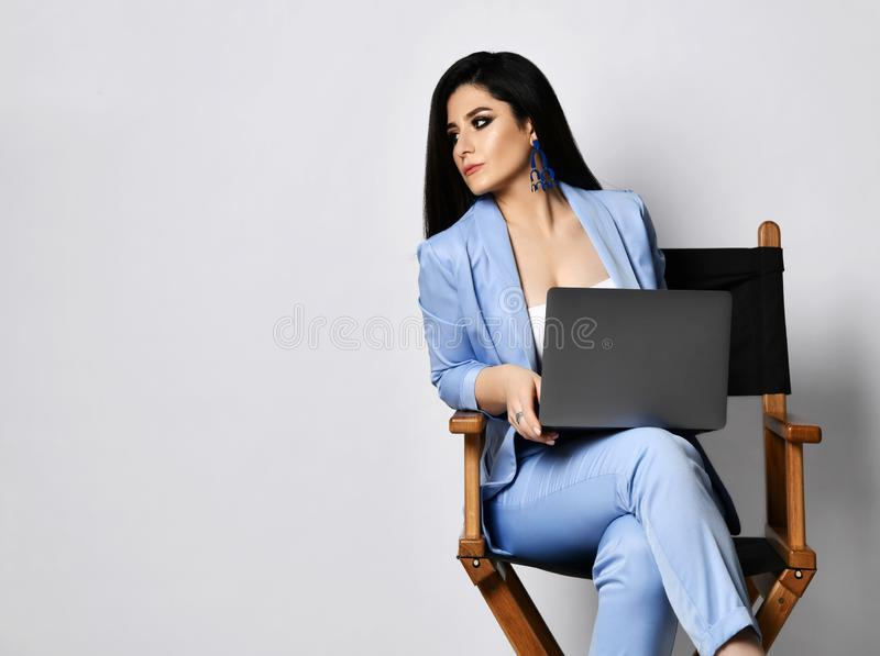 Strict business woman in blue formal wear sits with laptop on armchair looks sternly at something on the side of her stock image