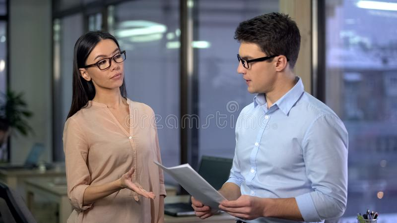 Strict business woman checking work of male trainee, demanding company boss royalty free stock image