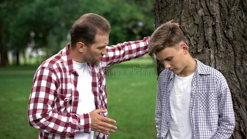 Strict dad scolding son for bad marks at school, parent respect, upbringing stock photography