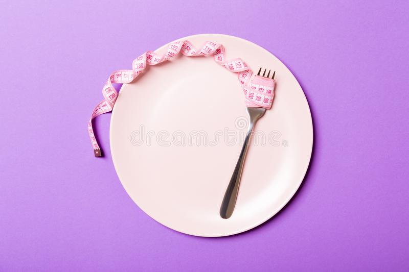 Strict diet concept with empty space fro your design. Top view of plate with fork in measuring tape on purple background royalty free stock photo