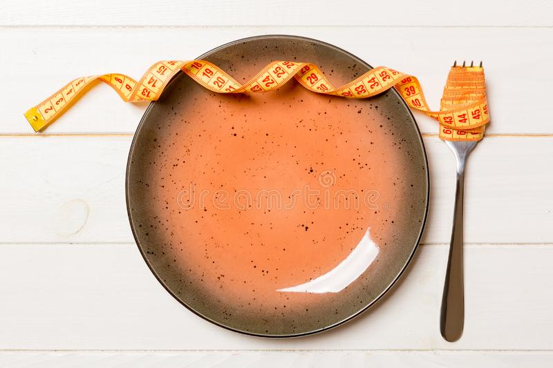 Strict diet concept with empty space fro your design. Top view of plate with fork in measuring tape on wooden background.  stock photos
