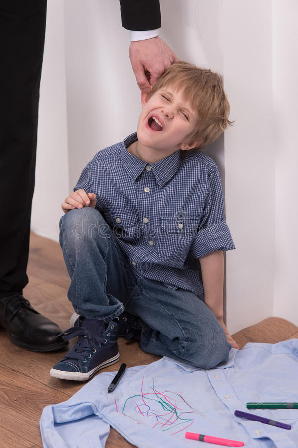 Strict father punishes naughty son. stock images