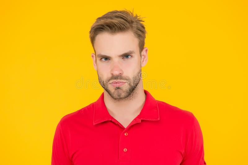 Strict glance. Handsome man unshaven face and stylish hair. Caucasian man on yellow background. Bearded man in casual. Style. Handsome guy portrait. Facial hair royalty free stock images