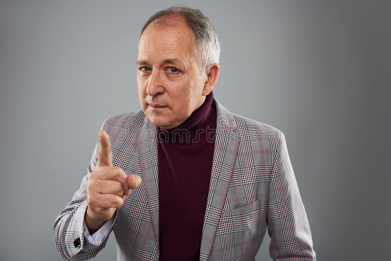 Strict man frowning and gesturing while asking for attention stock images