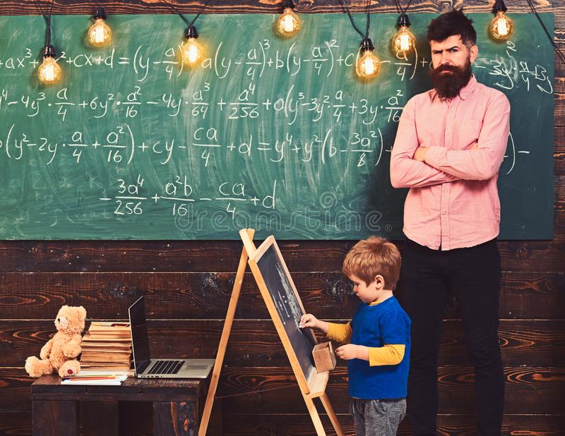 Strict math teacher checking pupil s work. Blond schoolboy solving equation at chalkboard. Preschool education concept stock image