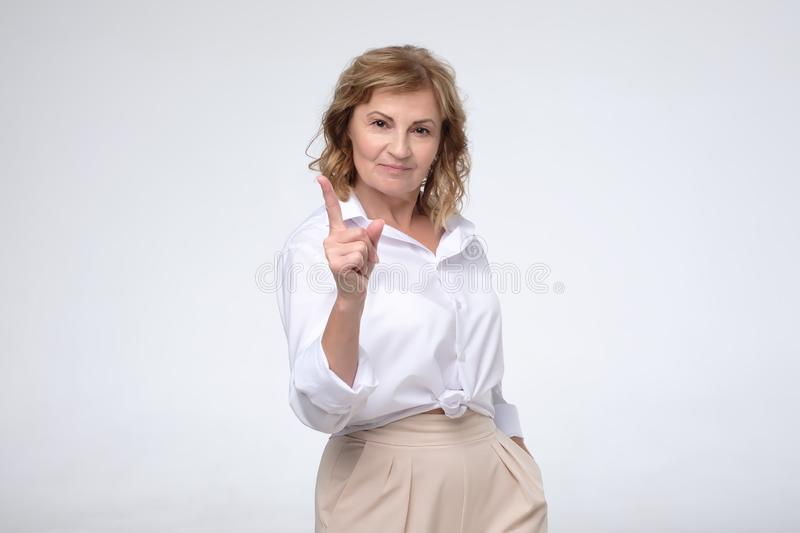 Beautiful middle age mature business woman pointing with finger up giving advice royalty free stock image