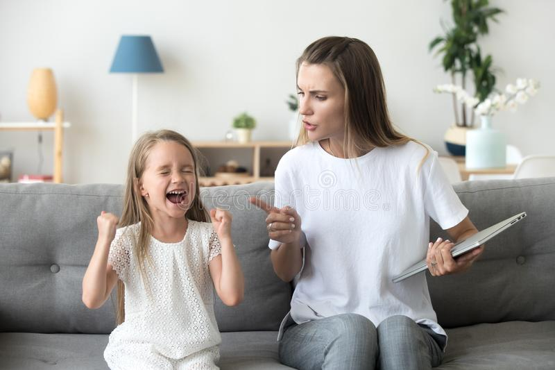 Strict mom scolding ill-behaved daughter screaming loud at home. Stubborn little girl scream loud not listening to strict mom, serious young mother scold stock photo