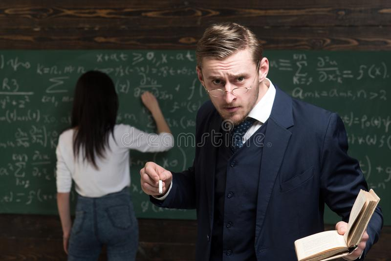 Strict professor looking at students over the glasses while holding book and piece of chalk in his hands. Female student stock images