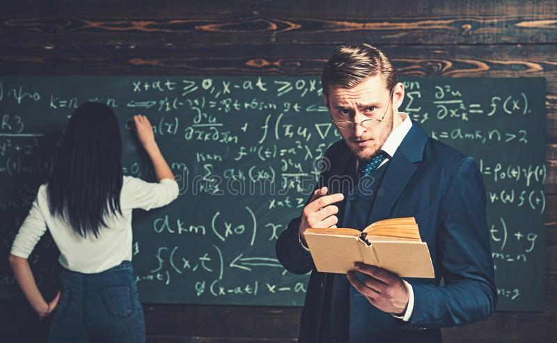Strict teacher in glasses giving explanations while holding book. Tutor helping his young female student with math stock image