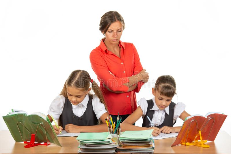 A strict teacher stands above the children who solve the task stock photography