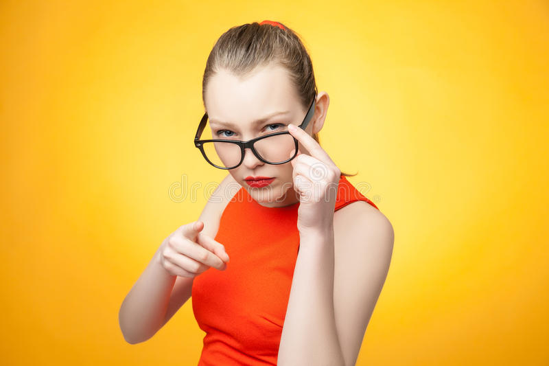 Strict woman pointing over orange royalty free stock image