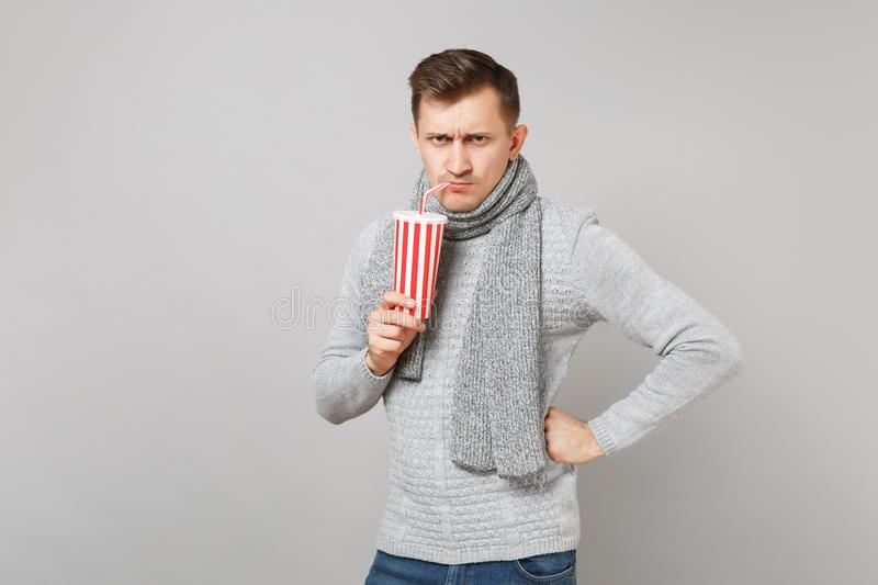 Strict young man in gray sweater, scarf drinking cola or soda from plastic cup on grey background. Healthy. Fashion lifestyle, people sincere emotions, cold stock photo