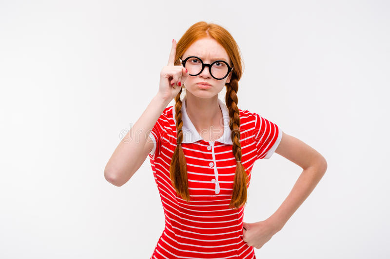 Strict young woman with two braids pointing up. Strict young redhead woman with two braids in round glassees pointing up isolated on white background royalty free stock image