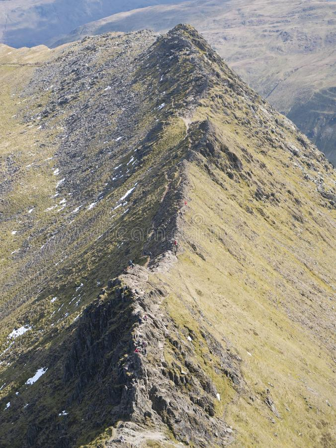 Striding Edge in the North West Lake District in Cumbria, England, UK. On a sunny day in spring with snow still visible: A popular route linking the summit stock photography