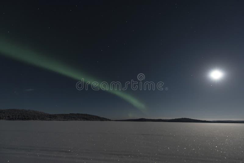Strie claire du nord verte à travers un ciel allumé par une lune superbe photographie stock