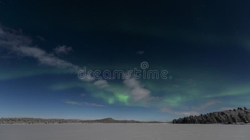 Strie claire du nord verte à travers un lac congelé images stock