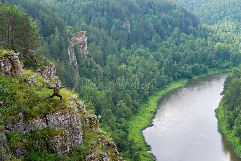 Strijder van de mensen backpacker stelt de praktizerende yoga op rand van de bergklip, Panorama aan de rivier royalty-vrije stock afbeelding
