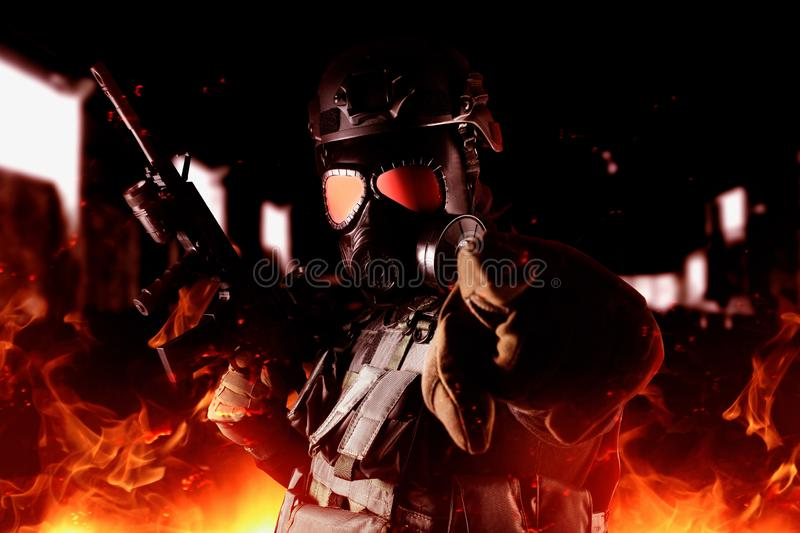 Strijdersmilitair in gasmasker en geweer die zich in brand bevinden stock fotografie