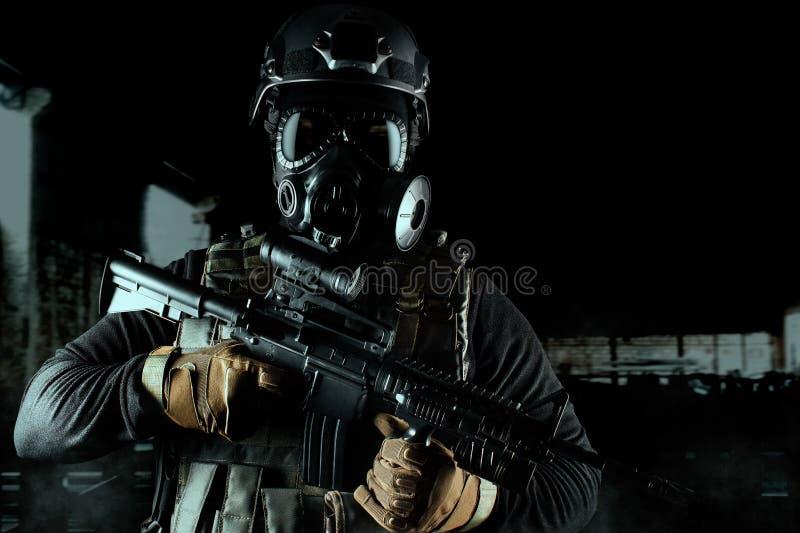 Strijdersmilitair in gasmasker en geweer op zwarte achtergrond stock afbeeldingen