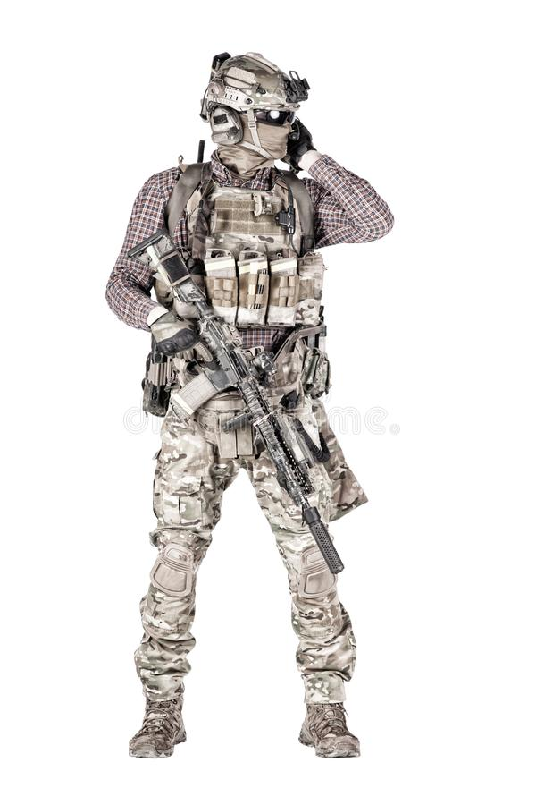 Softball player with military stuff studio shoot. Strikeball enthusiast in checkered shirt wearing military ammunition, face mask, helmet and radio headset royalty free stock photo