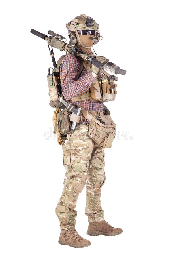 Softball player with military stuff studio shoot. Strikeball enthusiast in checkered shirt wearing military ammunition, face mask, helmet and radio headset stock photos