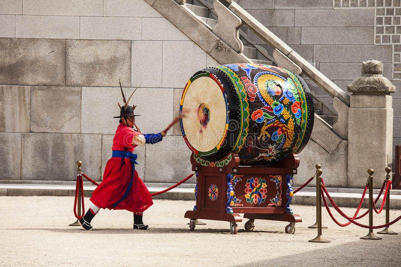 Striking The Ceremonial Drum. SEOUL, KOREA - APRIL 27, 2012: A guard is strking a giant ceremonial drum during the changing of the guard ceremony at the royalty free stock images
